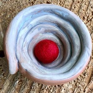 Kleines Tongefäss mit deutlich sichtbaren Schlangen, aus denen es geformt ist. Darin eine kleine rote Filzkugel.