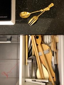 Eine offene Küchenschublade mit den aufgezählten Gegenständen und mehr, alles durcheinander geworfen. Auf der schwarzen Ablage liegen die vergoldeten Löffel, unscharf auf dem dunkelgrauen Steinboden ein roter Faden.