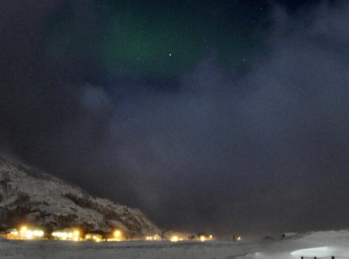 Nachts ein Schnee bedeckte Landschaft, links eine Lichterkette von Häusern am Rande der Ebene vor einem Hügel. Am Himmel hellgraublaue Wolken mit einer Lücke in der oberen Bildmitte, wo grünes Nordlicht schimmert um einen hellblauer Stern.