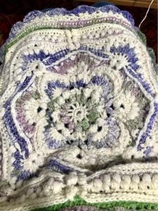 Viereckige Decke, mit vielen Mustern von innen nach aussen gearbeitet.  Es wechseln sich naturweisse, grünrosa gemischte und violettgrün gemischte Wollen ab.
